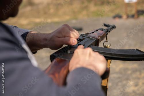 Photo Close-up military ak-47 weapon man loading weapon