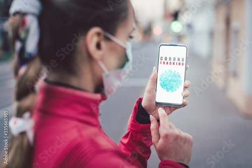 Woman using a phone with the coronavirus tracking app installed Canvas Print