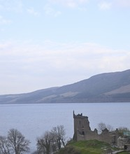 Vertical Picture Of The Urquhart Castle Surrounded By Loch Ness In Scotland