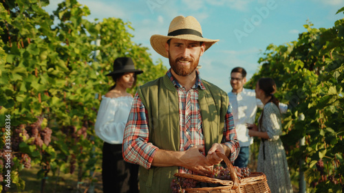 Portrait of proud caucasian farmer in strawhat smiling with joy holding large basket of grapes working during harvest in vineyard Poster Mural XXL