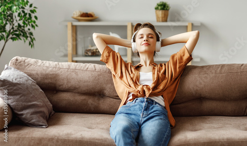 Pleased young woman in headphones listening to music while relaxing on sofa at h Fototapet