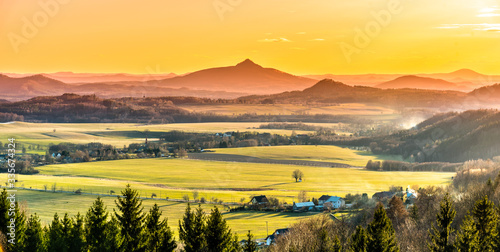 Fototapeta krajobraz   hilly-landscape-illuminated-by-evening-sunset-green-grass-fields-and-hills-on-the-horizont-vivid-spring-rural-countryside-ralsko-mountain-czech-republic
