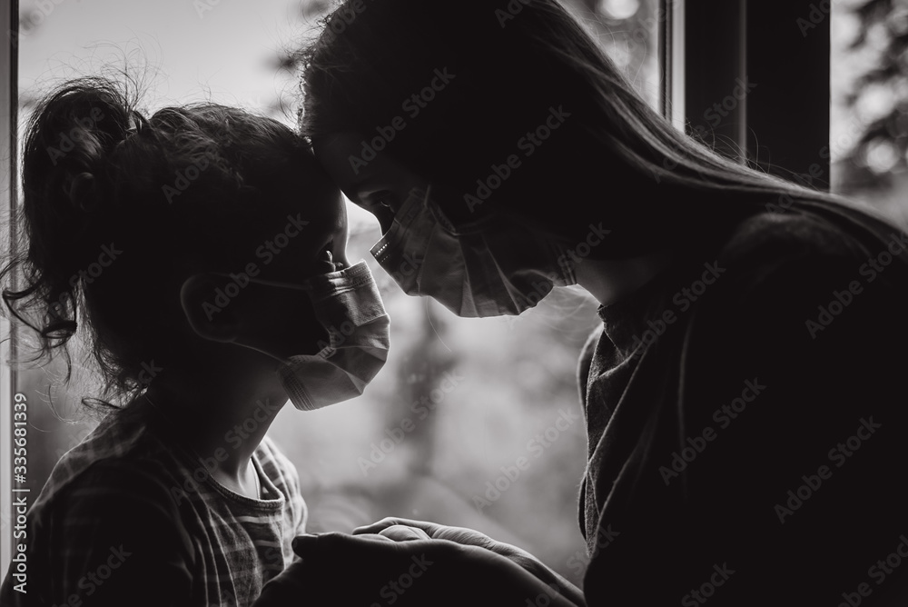 Fototapeta Black and white portrait of loving mother embracing upset little daughter with virus mask, young mom comforting, consoling sad preschool girl. Concept of coronavirus or COVID-19 pandemic