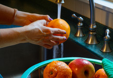A Woman Washes Citrus Fruit In A Kitchen Sink