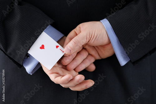 Photo Close up man suit holds ace card behind his back