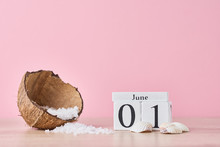 Wooden Block Calendar With Date June 1 And Coconut With Sea Salt On The Pink Background. Summer Vacation Concept