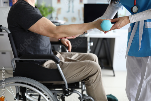 Photo Female nurse helps lift dumbbell to disabled patient rehabilitation therapy concept