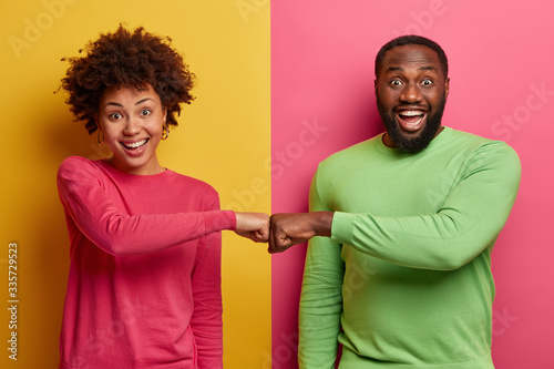 Happy dark skinned ethnic woman and man make fist bumps, work as team, agree to do something, smile positively, pose against bright two colored background Canvas Print