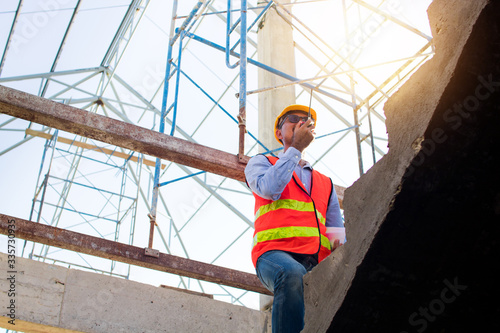 Fototapeta Engineer or inspector checking progressing work in construction site obraz