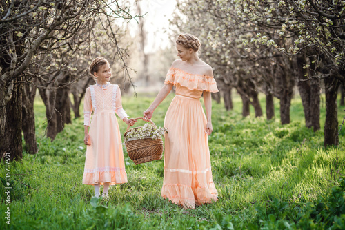 Obraz Two sisters are walking in the garden, - fototapety do salonu