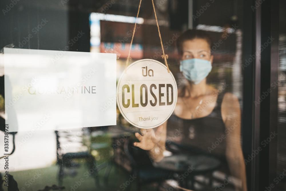 Fototapeta Store Owner in medical mask closed restaurant for quarantine