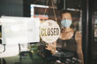 Store Owner in medical mask closed restaurant for quarantine