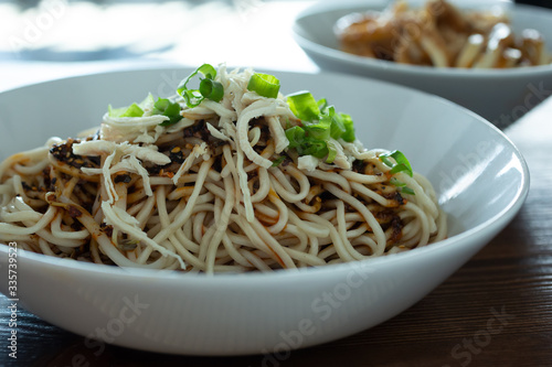 A view of a bowl of dan dan noodles with shredded chicken, in a restaurant or kitchen setting Fototapeta