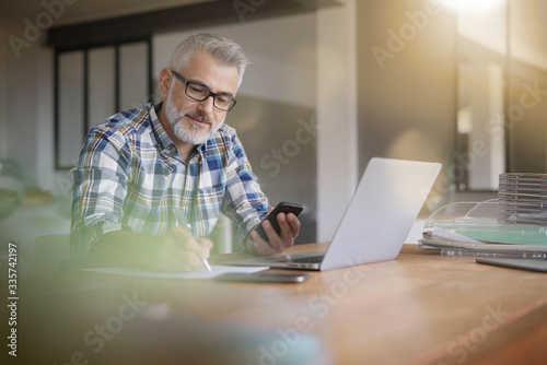 Canvastavla Man working from home with laptop and smartphone