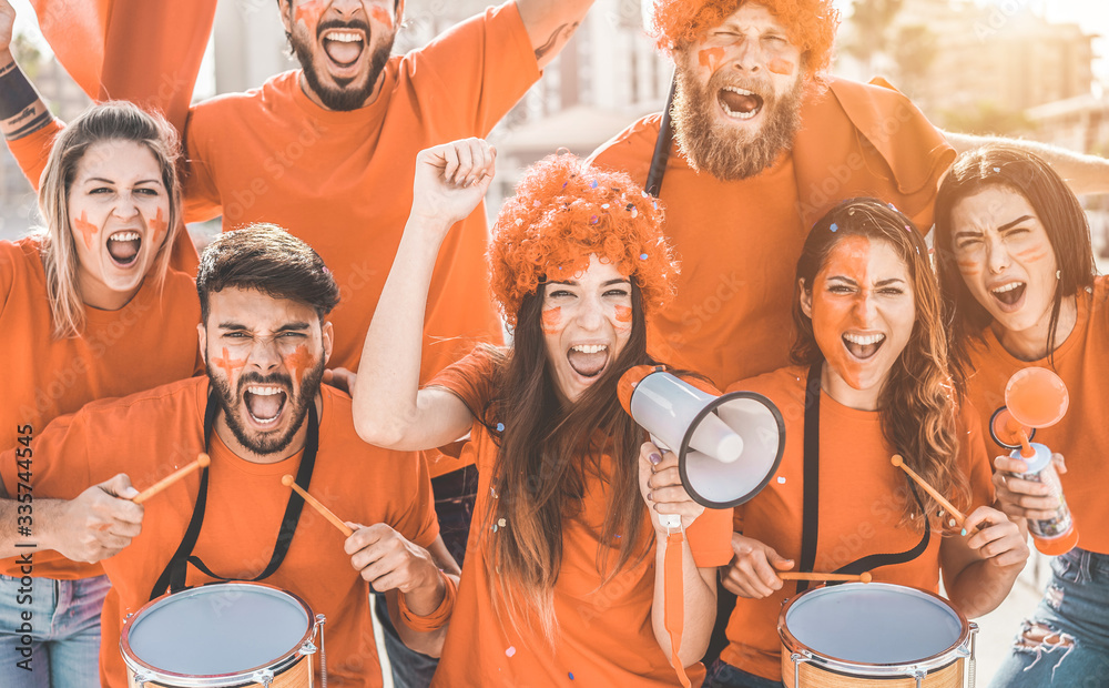 Fototapeta Orange sport fans screaming while supporting their team - Football people supporters having fun at competion event - Champions, betting and winning concept - Focus on center girl face