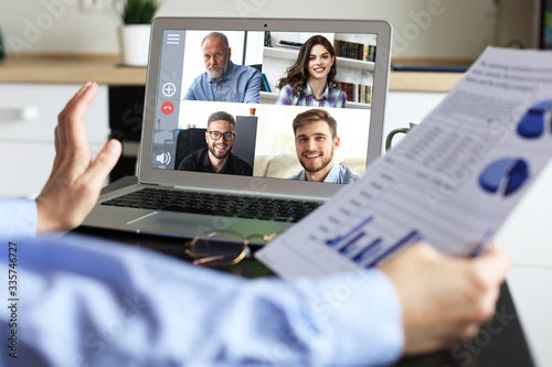 Obraz Business woman talking to her colleagues in video conference. Business team working from home using laptop. - fototapety do salonu