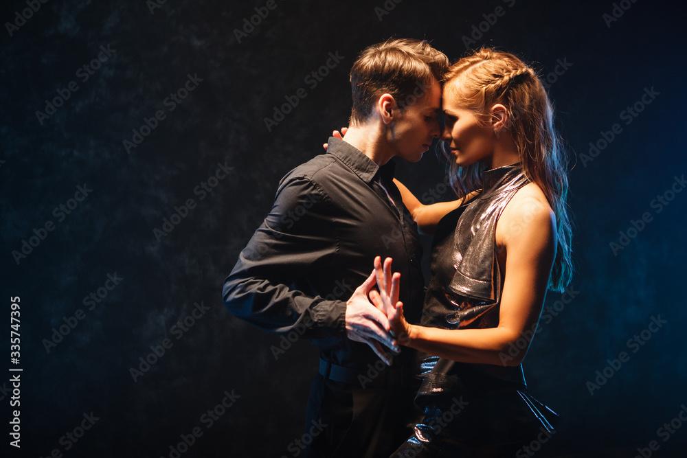 Fototapeta young couple in elegant evening dresses dancing
