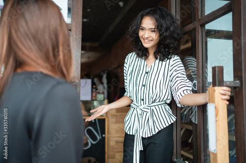 Photo young attractive asian fashion shop owner at her store opening the door for cust