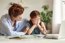 Kind Mother Embracing And Comforting Small Crying Daughter Having Difficulties With Homework While Sitting At Table And Doing Exercise In Copybook In Cozy Apartment.