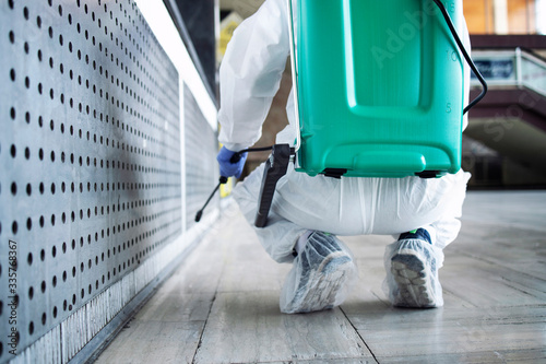 Photo Unrecognizable person in white protection suit disinfecting public areas to stop spreading highly contagious coronavirus