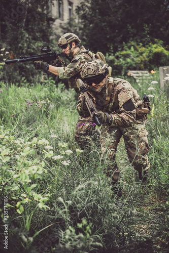 Fotografía Two men in military camouflage vegetato uniforms with automatic assault rifles