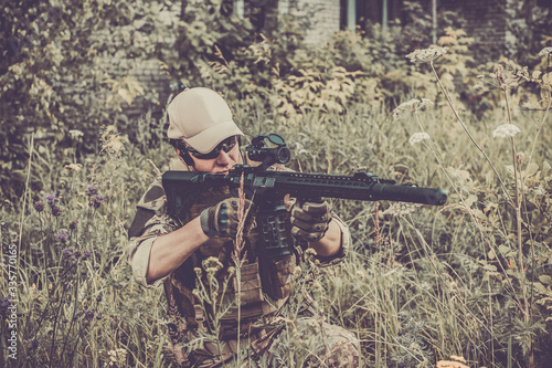 Fotomural A military man or airsoft player in a camouflage suit sits in the grass and aims