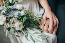 Wedding. The Girl In A White Dress And A Guy In A Suit Sitting On A Wooden Chair, And Are Holding A Beautiful Bouquet Of White, Blue, Pink Flowers And Greenery, Decorated With Silk Ribbon