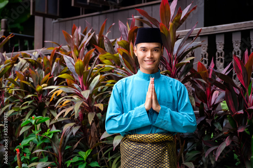 Fotografía A portrait of young malay man in his traditional teal cloth, samping songket and songkok