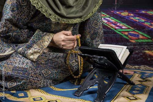 Muslim woman praying for Allah muslim god at room near window Fototapeta