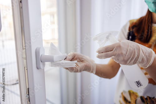 Obraz Corona virus prevention, cleaning woman wiping doorknob with antibacterial cleanser for killing coronavirus on touching surfaces. - fototapety do salonu