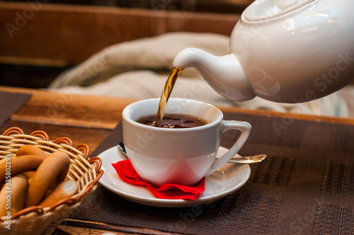 Pouring fresh tea from porcelain tea kettle into white cup Canvas Print