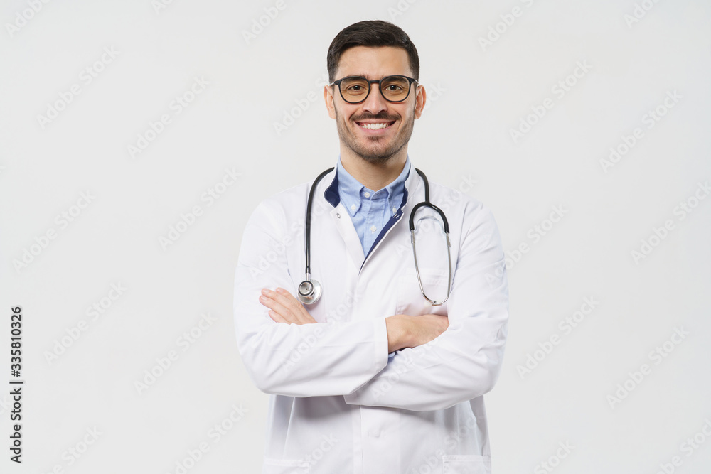 Fototapeta Portrait of smiling young male doctor with stethoscope around neck standing with crossed arms in white coat, isolated on gray background