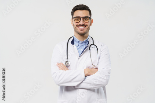 Canvastavla Portrait of smiling young male doctor with stethoscope around neck standing with