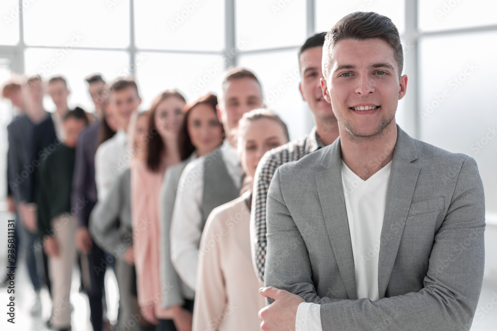 Fototapeta confident guy standing in line of diverse young people