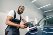 Smiling handsome young black skinned man, professional worker of car detailing service, polishing blue car with polishing machine and microfiber cloth. Car detailing, polishing, finishing concept