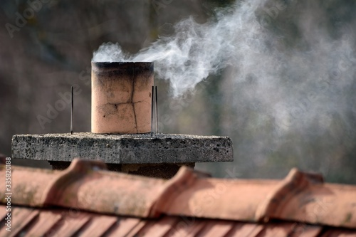 Canvastavla Closeup of smoke coming out of a chimney on the building under the sunlight at d