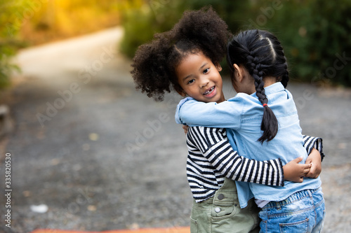 Obraz Summer camp travel trip. Two little cute child girls hugging each other with love. Little Girl Children Smiling Happiness Friendship - fototapety do salonu