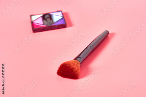 Vászonkép Palette of colorful blush made from natural components near brush for cosmetic powder lies on pink countertop in salon