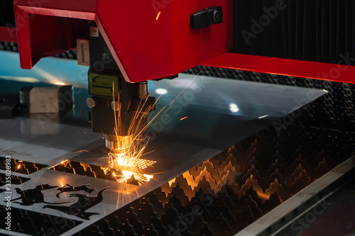 Photo The fiber laser cutting machine cutting the sheet metal  plate with the sparkling light
