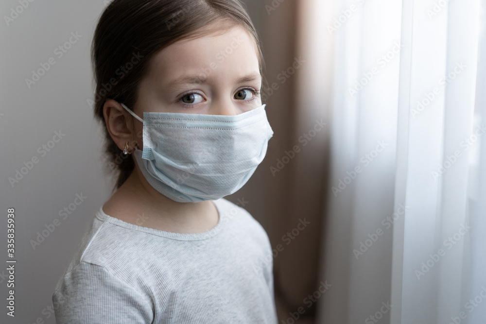 Fototapeta Little european girl wearing mask for protect Covid-19. Sadness child at home in isolation