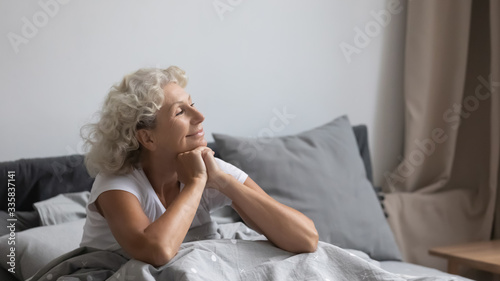 Fotografía Peaceful calm positive middle aged senior retired woman sitting in bed after wakeup in weekend morning, enjoying good mood after good night rest relaxation, welcoming new day alone in bedroom