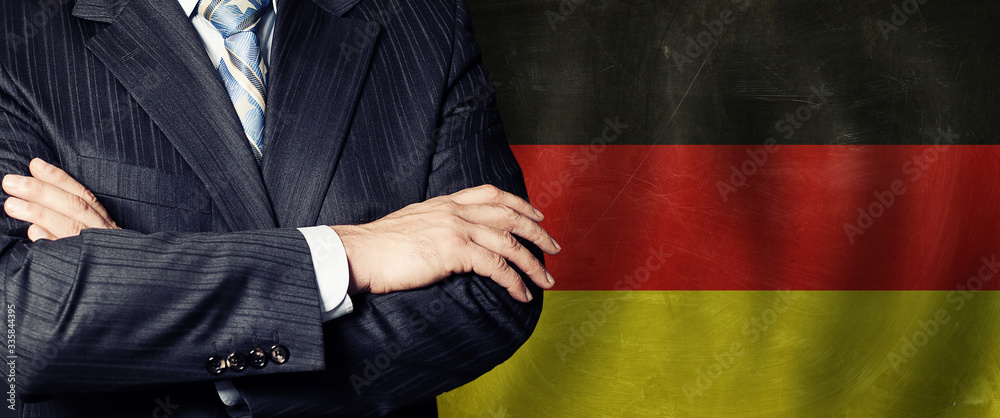 Fototapeta Male hands against German flag background, business, politics and education in Germany concept