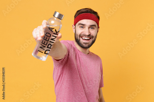 Cheerful young bearded fitness sporty guy 20s sportsman in headband t-shirt spend weekend in home gym isolated on yellow wall background Canvas Print