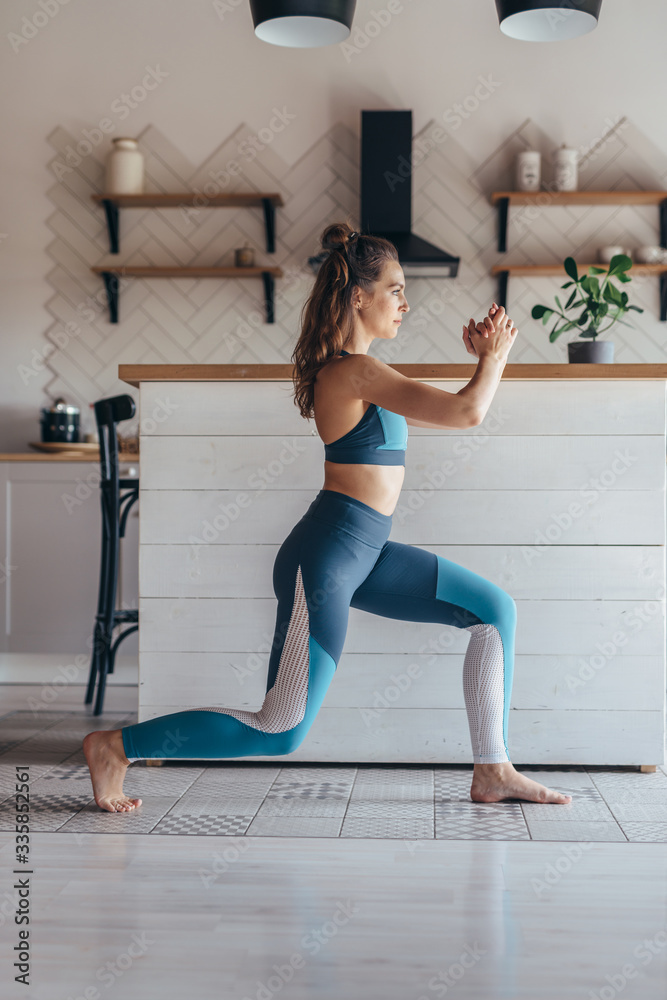 Fototapeta Fit woman exercising at home doing lunges exercise.