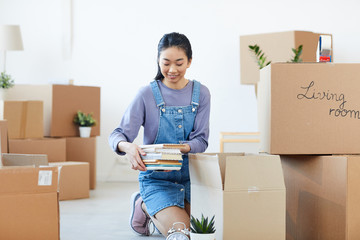 Full length portrait of young Asian woman packing books to cardboard boxes and smiling happily excited for moving to new house or dorm, copy space