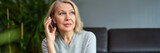 Fototapeta Zwierzęta - Beautiful mature blond woman talking on mobile phone at sofa.