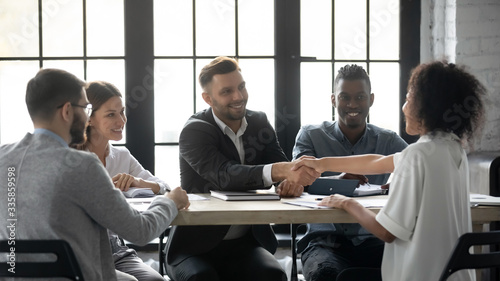 Obraz na plátně Happy successful businessman in suit shaking hand of african american businesswoman at company meeting