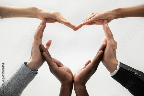 Cuadros en Lienzo Close up bottom view concept of diverse business people join hands forming heart