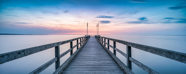 Panoramic view of a wooden pier during sunset at the sea
