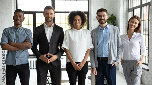 Portrait of standing in row smiling diverse team posing differently looking at camera. Happy young multiethnic corporate staff, bank workers photo shoot, HR agency recruitments.